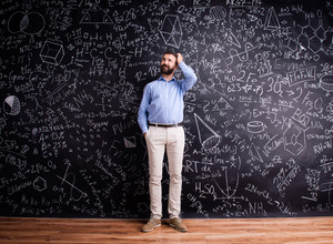 Hipster teacher scratching head, standing against big blackboard with mathematical symbols and formulas. Studio shot on black background.