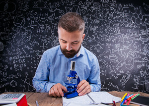 Hipster teacher sitting at the desk with microscope and other school supplies against big blackboard with formulas and mathematical symbols