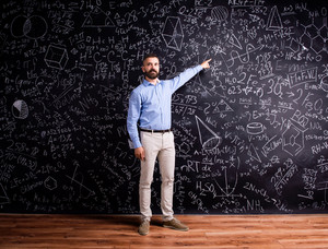 Hipster teacher standing against big blackboard with mathematical symbols and formulas. Studio shot on black background.