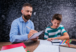 Hipster teacher with his student sitting at the desk with calculator, exercise book and other school supplies against big blackboard with formulas and mathematical symbols