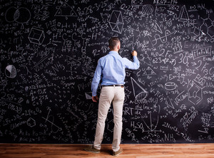 Hipster teacher writing on big blackboard with mathematical symbols and formulas. Studio shot on black background. Rear view