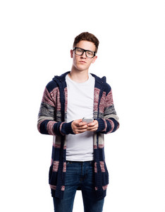 Hipster teenage boy in eyeglasses, jeans and striped sweater, holding smart phone, texting. Young man. Studio shot on white background, isolated.
