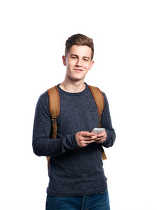 Hipster teenage boy with backpack on his back, wearing sweater holding smart phone, texting. Young man. Studio shot on white background, isolated.