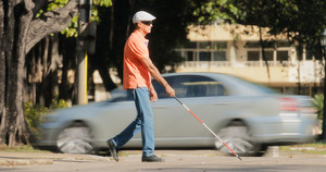 Hispanic blind man, latino people with disability, handicapped person and everyday life. Visually impaired man with walking stick, crossing the street with cars and city traffic