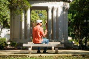 Hispanic blind man, latino people with disability, handicapped person and everyday life. Visually impaired man with walking stick, sitting on bench in city park