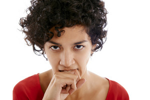 hispanic frustrated woman biting fingers, angry, looking at camera