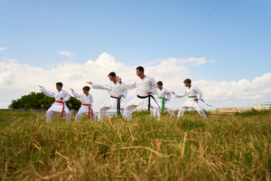 Hispanic men and children exercising in karate and traditional martial arts. Simulation of fight on the beach near the sea