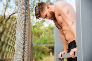 Hnadsome shirtless bearded sportsman doing workout outdoors