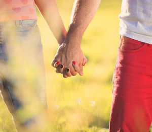 Holding hands of happy young couple having fun outside in a park
