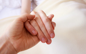 Holding the hand of a sick loved one in hospital bed