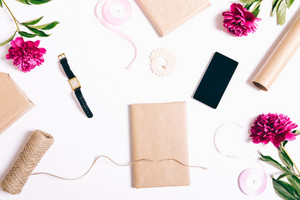 Holiday decorations on a white background: ribbons, packing paper, gifts, flowers, phone, wristwatch. Top view, preparation for holiday.
