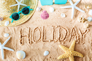 Holiday text in the sand with beach accessories