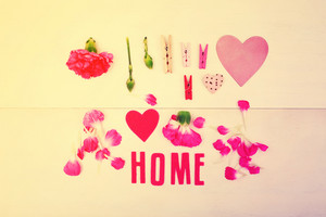Home text with clothespins and carnation flowers