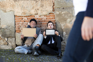 Homeless men are begging on the street.