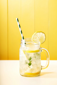 Homemade lemonade in a mason jar with big green striped straw