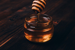 Honey dripping into jar on a table close-up