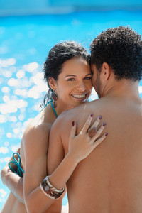 Honeymoon: happy young newlyweds smiling and relaxing near hotel pool. Vertical shape, waist up, copy space