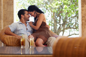 honeymoon: young just married hispanic couple sitting on armchair in hotel bar and hugging. Horizontal shape
