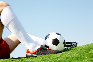 Horizontal image of seated player leg with soccer ball near by