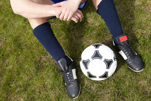 Horizontal image of seated player legs with soccer ball between