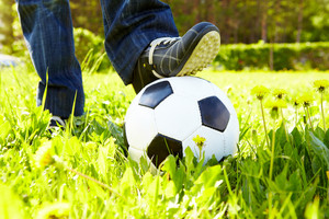 Horizontal image of soccer ball in green grass and shoes
