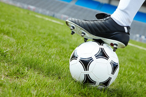 Horizontal image of soccer ball in green grass with foot of player touching it