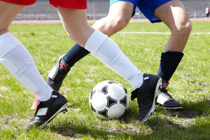 Horizontal image of soccer ball on the field with footballers legs near by