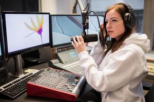 Host Adjusting Headphones And Microphone At Table In Radio Studi