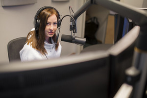 Host Wearing Headphones While Using Microphone In Radio Studio