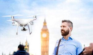 Hovering drone taking pictures of handsome young businessman in blue shirt on Westminster bridge next to Big Ben