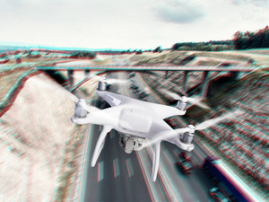 Hovering drone taking pictures of highway with cars and trucks, bridge and nature of Netherlands. Aerial view.