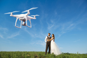 Hovering drone taking pictures of wedding couple in summer nature