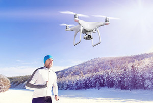 Hovering drone taking pictures of young handsome athlete running on snowy white meadow against forest and clear blue sky