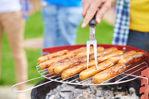 Human hand with fork frying sausages on grill at weekend