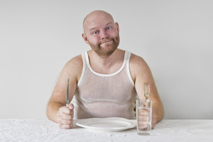 Hungry and happy man with no food on his plate. Perphas on a diet?