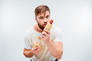 Hungry bearded man smelling hotdog isolated on white background