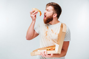 Hungry man eating slice of pizza isolated on white background