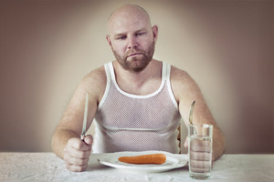 Hungry man with just a carrot on his plate. Perphas on a diet?