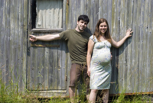 Husband with pregnant wife in front of their old house.