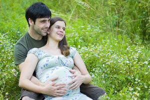 Husband with pregnant wife is resting in nature.