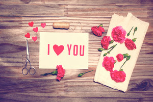 I Love You theme with scissors, twine, and carnation flowers on grungy background
