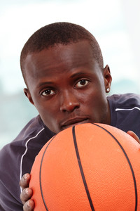 Image of a basketball player with ball looking forward