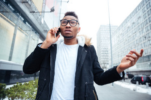Image of a confused african young man walking on the street while talking by his cellphone. Looking aside.