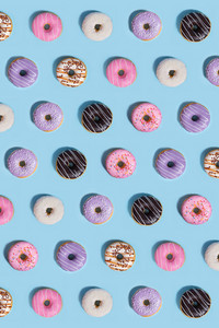 Image of a lot of colorful sweeties donuts over blue table background.