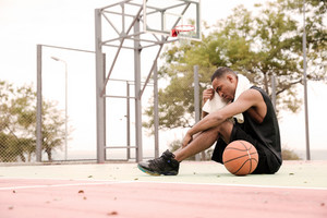 Image of a tired african basketball player sitting in the park with towel.