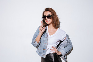 Image of a young cheerful lady wearing sunglasses dressed in jeans jacket standing isolated over white background while stretching bubble gum.
