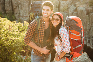 Image of adventure couple near the canyon. smiling happy couple