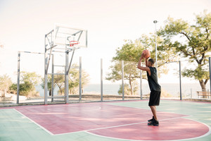 Image of african basketball player in the street with ball. Looking at basketball hoop.