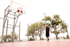 Image of african basketball player practicing in the street with trees on background. Look at basketball hoop.