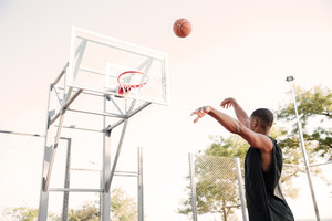 Image of african basketball player practicing in the street with trees on background. Looking at basketball hoop.